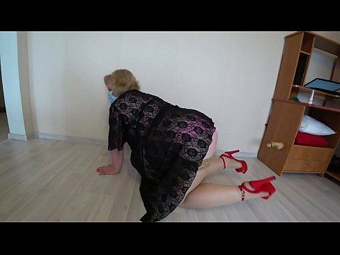 Зріла блондинка в сексуальному вбранні, в панчохах, в туфлях на високих підборах, демонструє пухку ф